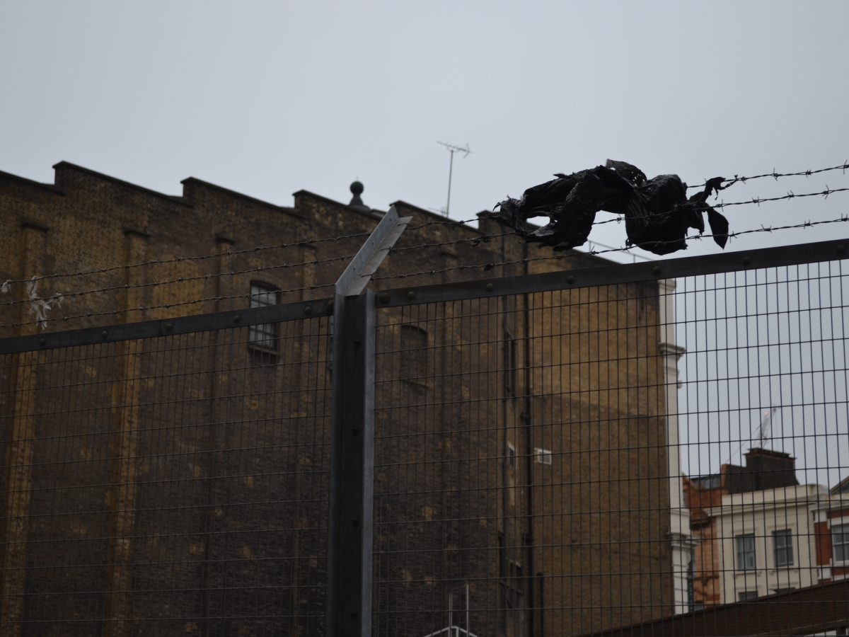 A bin bag stuck on barbed wire, over a railway bridge in King's Cross, London