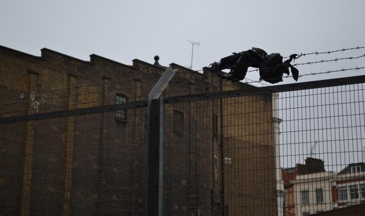 A bin bag stuck on barbed wire, over a railway bridge in King's Cross, London